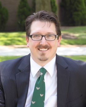 Headshot of Paul taken outside in nature. He is wearing a blue suit, a green tie, and glasses