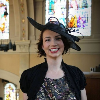 Jen in a church in semi-formal clothing with a jaunty black hat on, smiling
